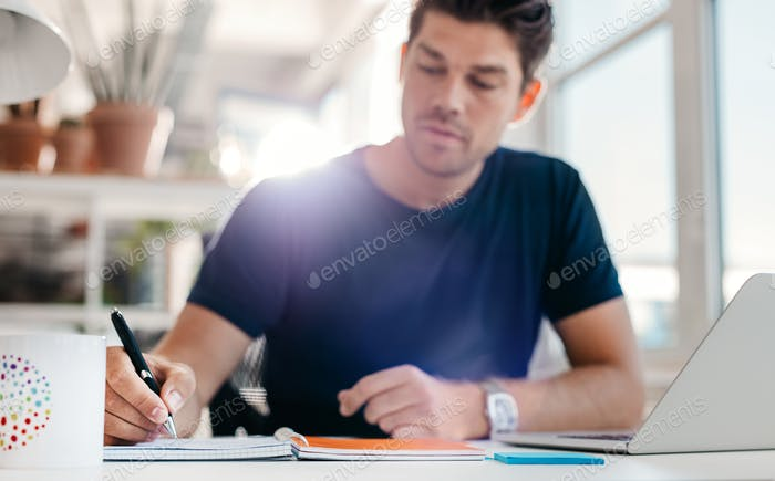 Junger Mann sitzt am Schreibtisch Schreibnotizen