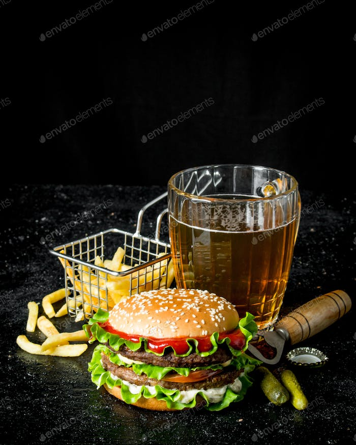 Burger with beer, fries and gherkins.