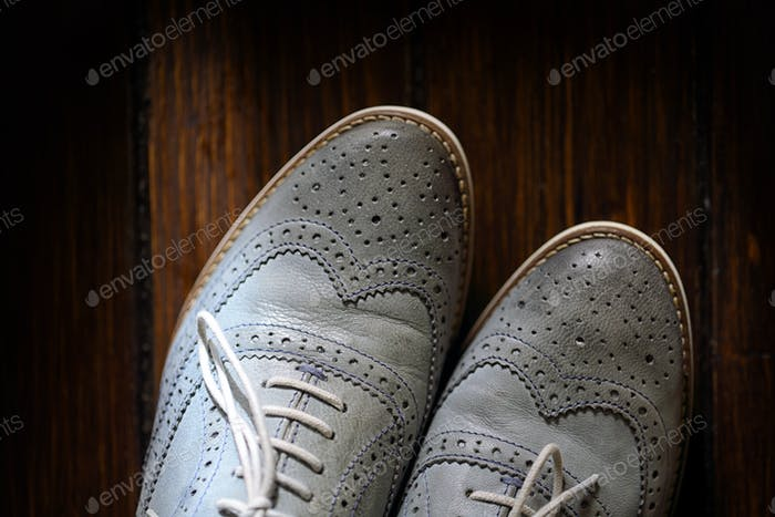 Grey oxford shoes on wooden background