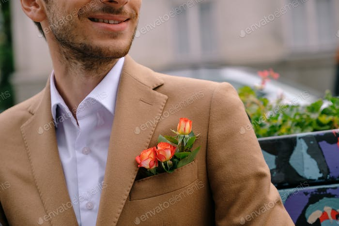 Close-up man dressed in classy jaket with three roses in poket