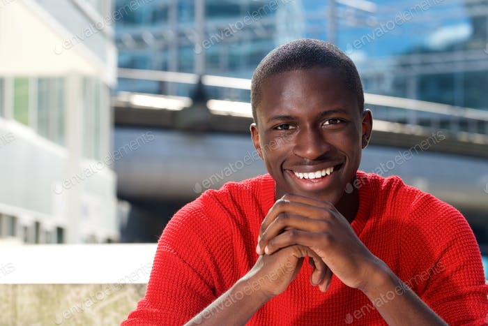 Handsome young black guy sitting outdoors and smiling