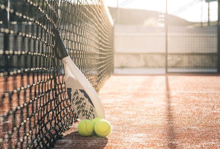 Padel blade racket resting on the net