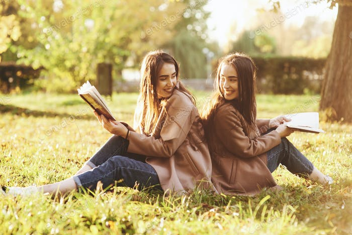 Smiling brunette twin girls sitting back to back on the grass