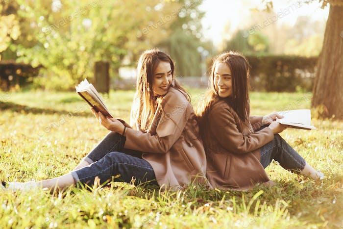 Lächelnde brünette Zwillingsmädchen, die Rücken an Rücken auf das Gras