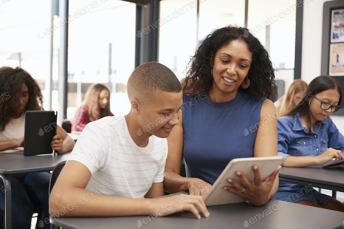Lehrer helfen Teenager Schuljunge mit Tablet-Computer