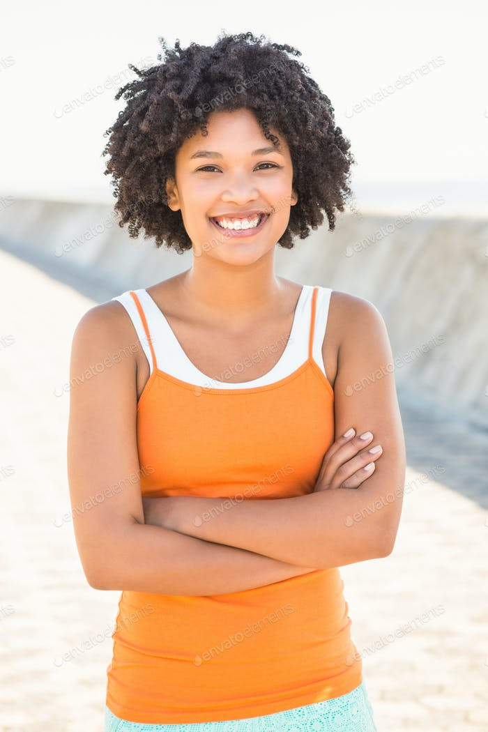 Portrait of young sporty woman smiling to camera at promenade