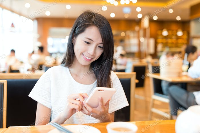 Woman using mobile phone at chinese restaurant