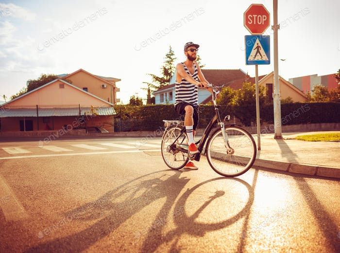 Stylish man in sunglasses riding a bicycle on a city street at s