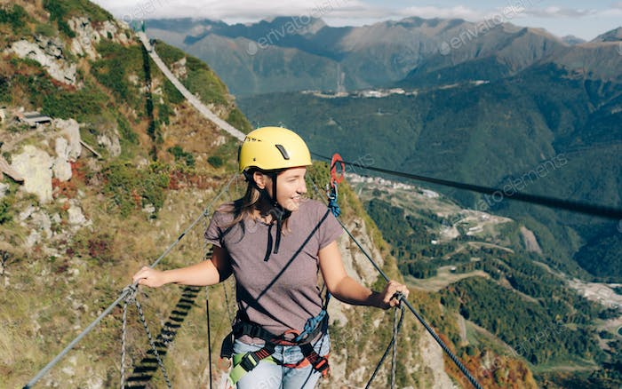 Young bold extreme woman in equipment and helmet walks in the mountains on a suspension bridge