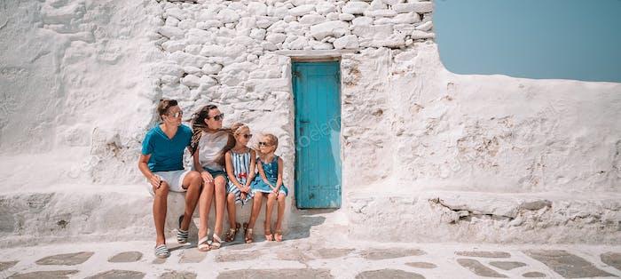 Eltern und Kinder auf der Straße des typisch griechischen traditionellen Dorfes auf Mykonos Insel, in Griechenland