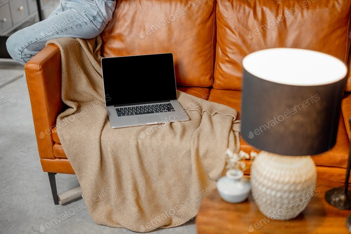 Open laptop lying on foxy leather sofa at home