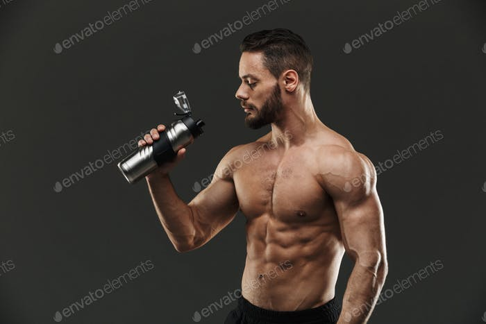 Portrait of a strong muscular bodybuilder drinking water