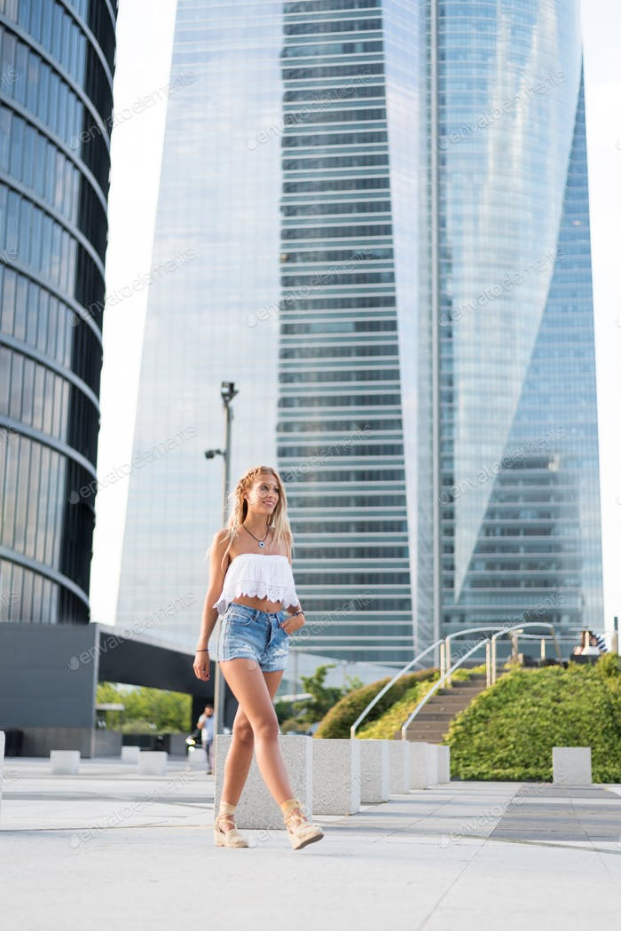 beautiful blonde woman wearing short jeans walking on the street