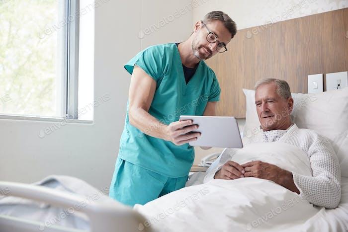 Chirurg Mit Digital-Tablette Besuch Senior Männlichen Patienten Im Krankenhaus Bett In Geriatrische Einheit