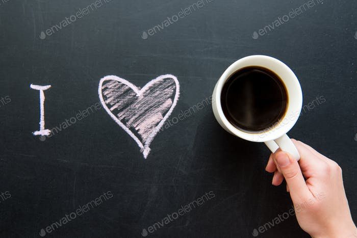 Top view of I love heart doodle drawing on chalkboard with human hand holding cup of coffee