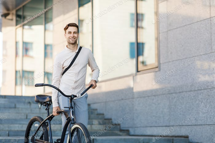 Convenient transport in city. Businessman walking down stairs with bicycle