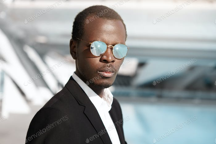 Outdoor portrait of attractive confident 30-year old African American businessman wearing black form