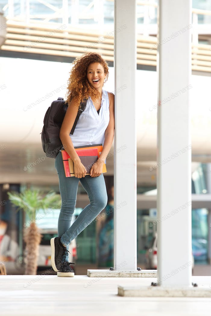 Full body happy female student standing outside with books and bag