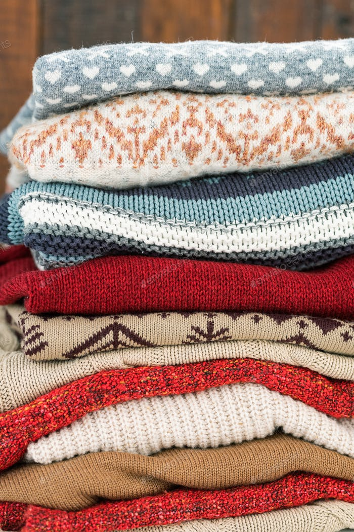 Knitted sweaters of various colors with ornaments ready for autumn and winter