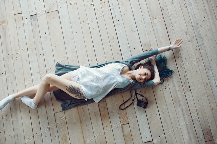 Beautiful carefree young casual woman lying on the wooden floor