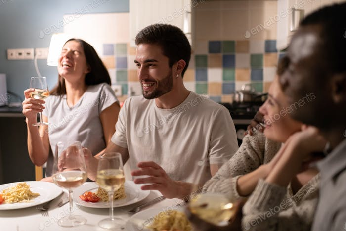 Young man telling stories to diverse friends during party