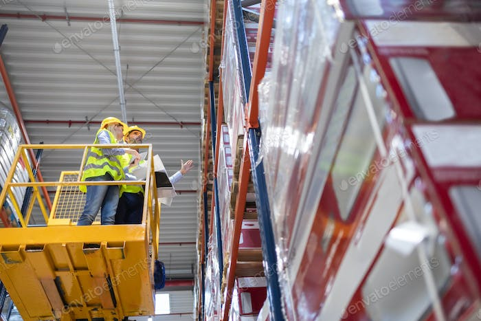 Warehouse workers on lift work platform checking inventory