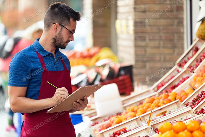 Handsome young salesman doing inventory in health grocery shop.