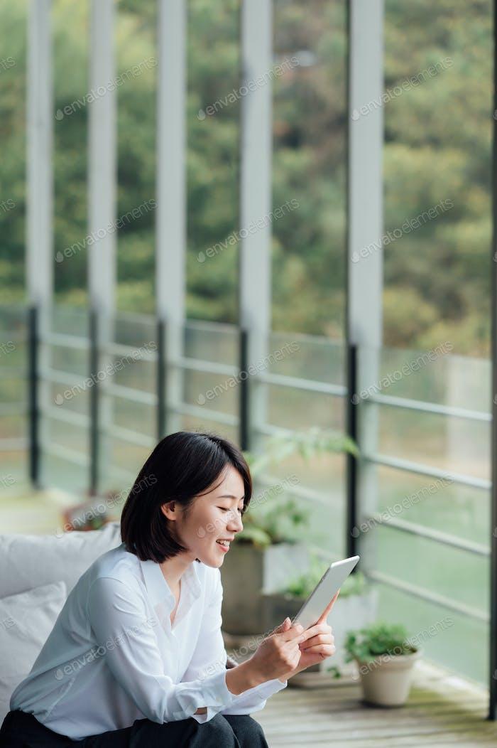 Asiatische Geschäftsfrau mit ipad am Bürofenster