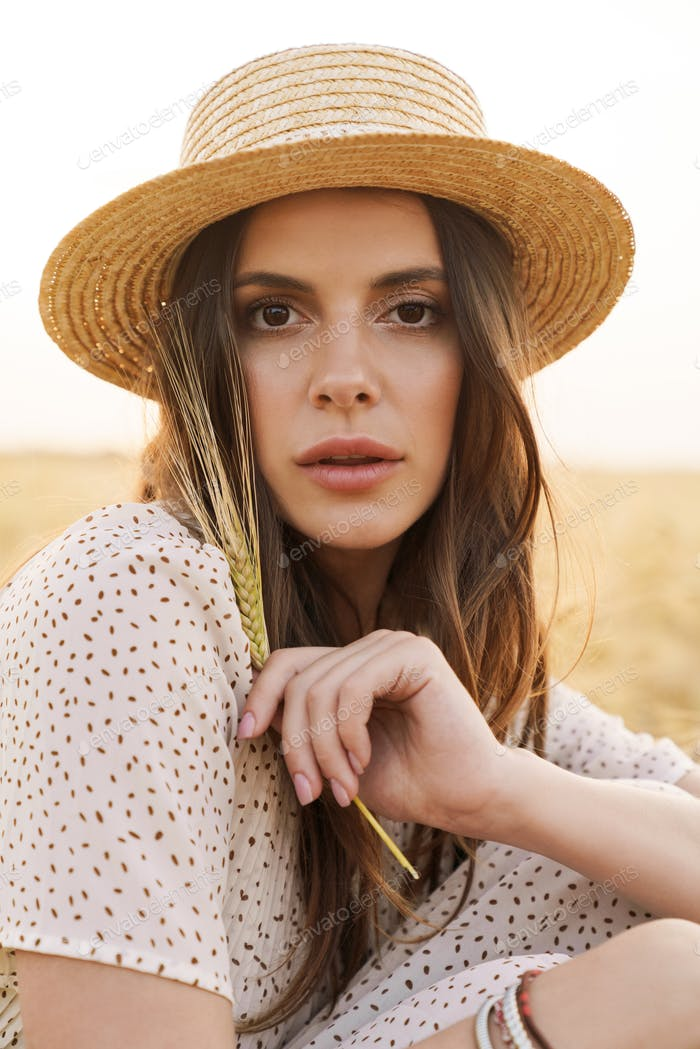 Photo of charming caucasian woman resting while sitting on wheat field