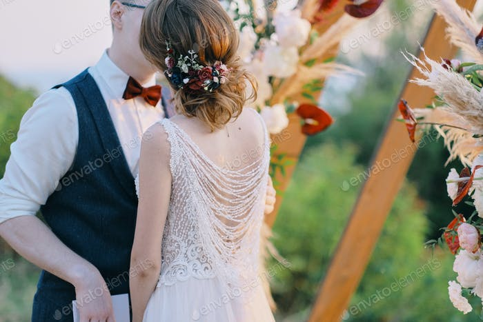 Beautiful moment from a wedding ceremony in nature. The bride and groom hold each other's hands.