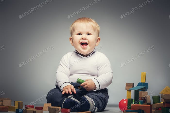 Giggling child sitiing on the floor with toys.