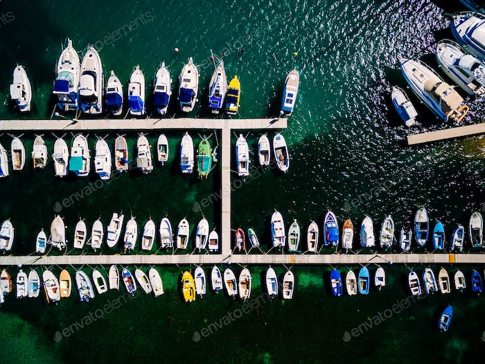 Aerial view of boats lined up on the piers at a marina.