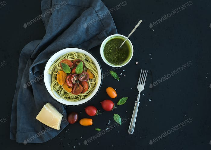 Pasta spaghetti with pesto sauce, basil, slow-roasted cherry-tomatoes in rustic metal bowl