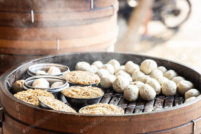 Steamy hot dim sum fish ball and glutinous rice in steam tray at Chinese restaurant