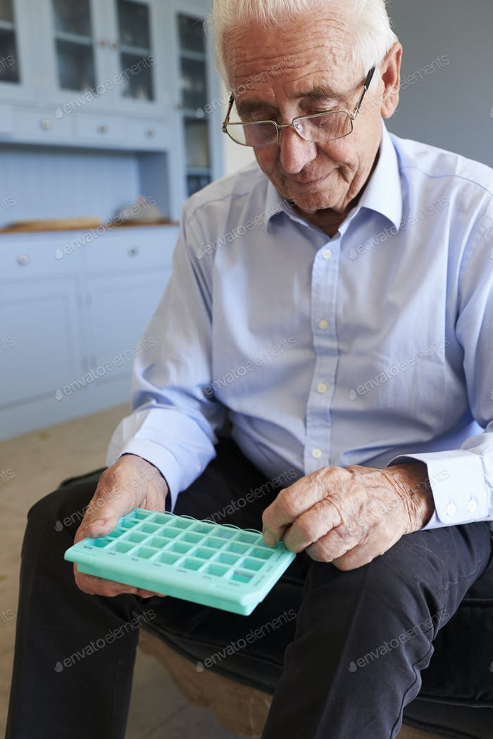 Senior Man At Home Using Pill Organiser For Medication