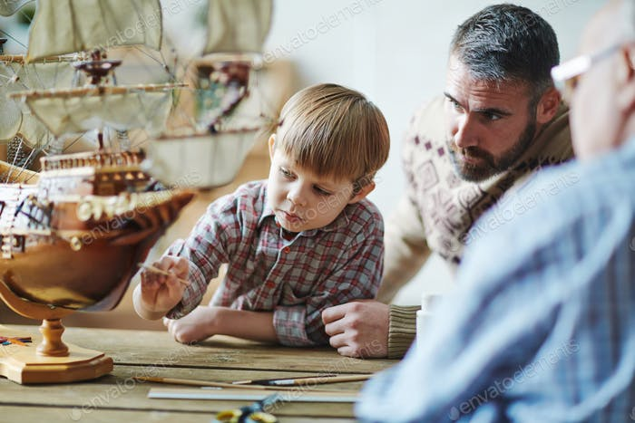 Painting toy ship with father