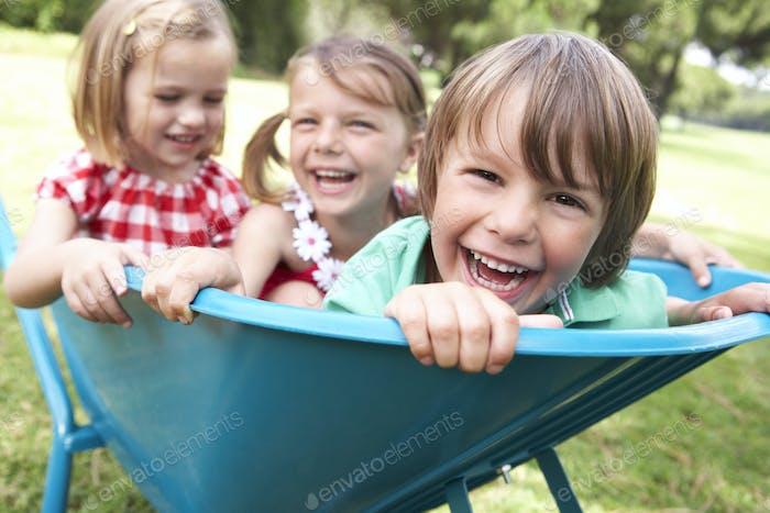 Drei Kinder sitzen in Schubkarre