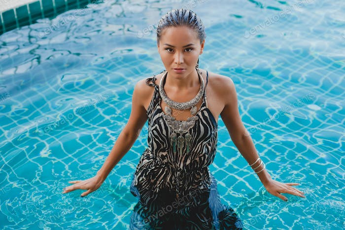 young asian sexy beautiful woman in tropical dress, zebra print, posing in pool