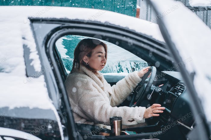 Attractive woman driver nsitting behind the steering wheel in her car
