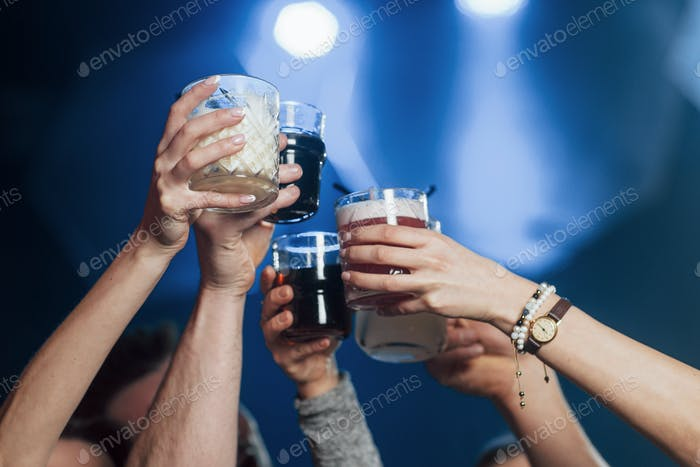 Hands only. Group of young friends making a toast in the nightclub