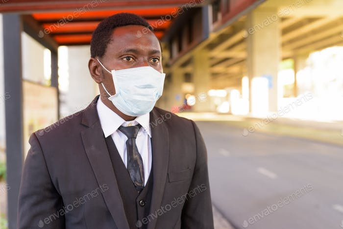 African businessman with mask thinking while waiting at the bus stop