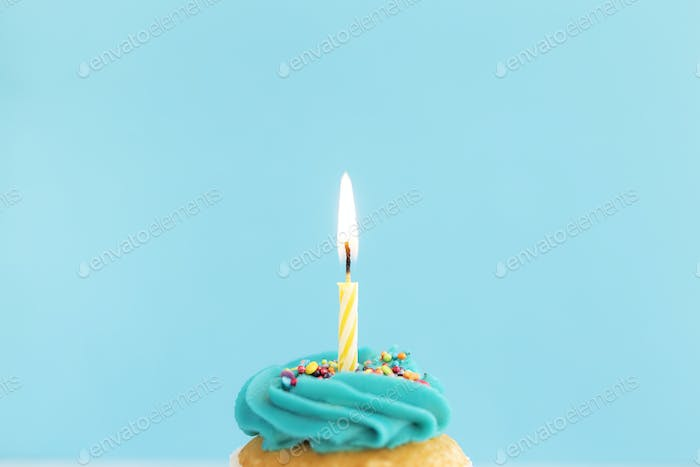 Birthday greeting concept. Burning candle on muffin, cupcake. Blue background