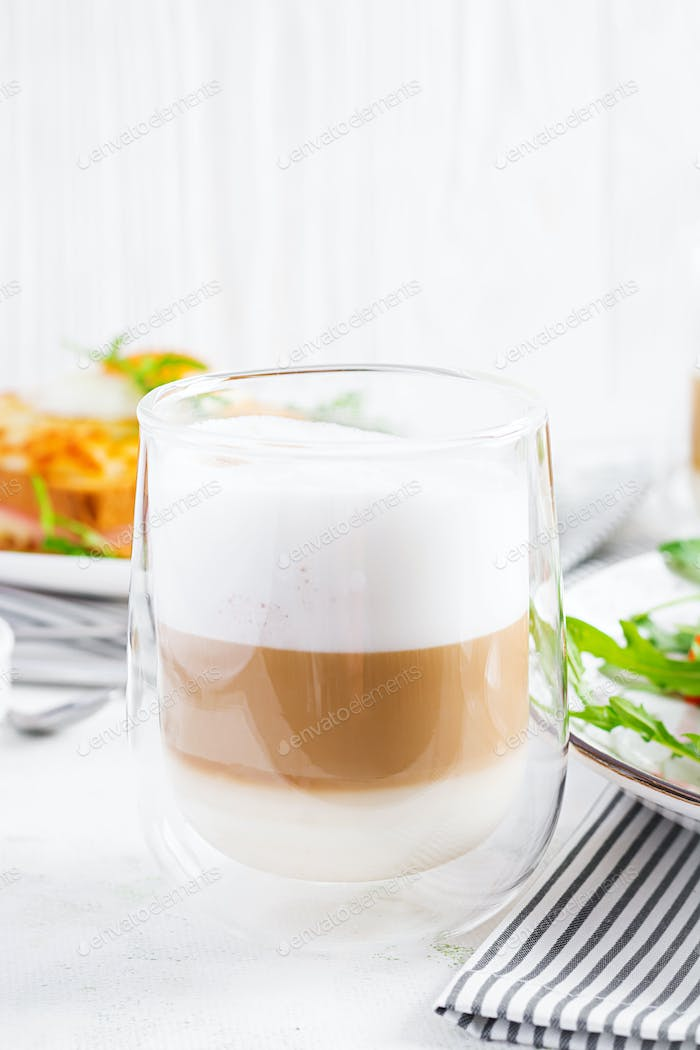 Coffee cafe latte macchiato in a glass on  light background. Italian cuisine