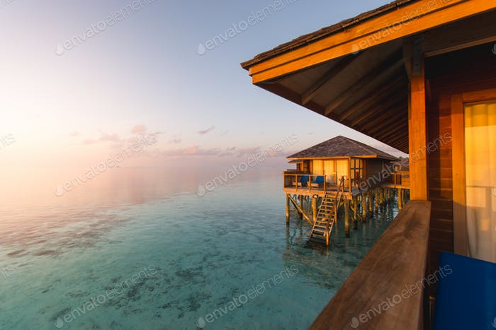 Beautiful tropical Maldives resort hotel and island with beach and sea on sky sunset.