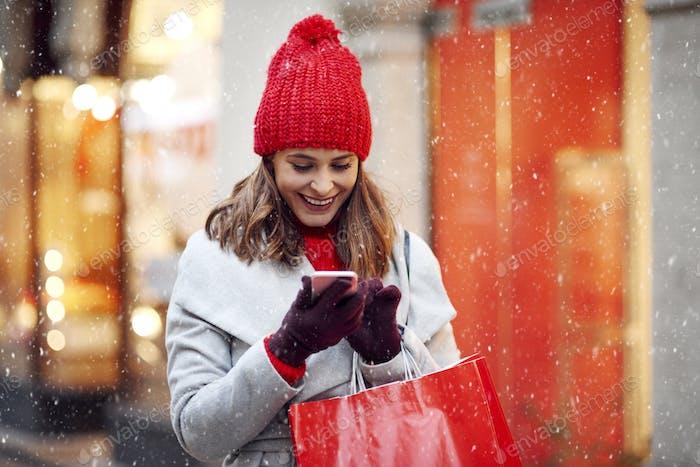 Schöne Frau mit Handy beim Einkaufen im Winter