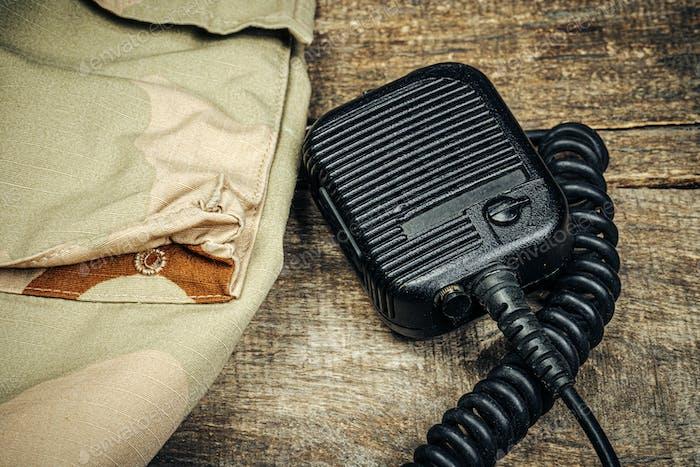 Militärausrüstung, Walkie-Talkie mit Militäruniform auf Holzbrett