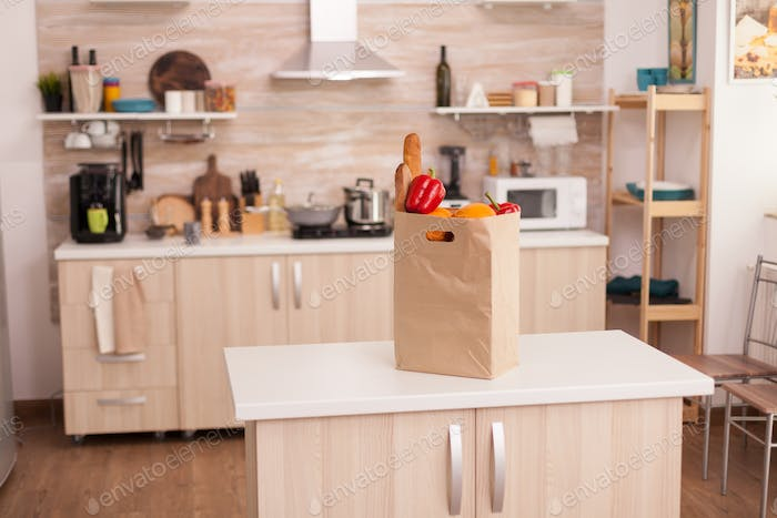 Paper bag filled with groceries on kitchen table top
