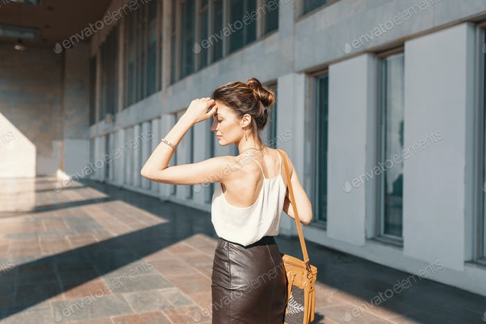 Refined young woman in leather skirt and silk blouse thinking how to solve a situation.
