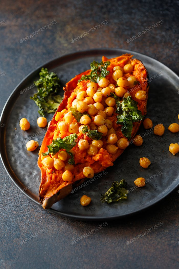 Baked sweet potato stuffed with chickpea and crunchy kale on a black plate.