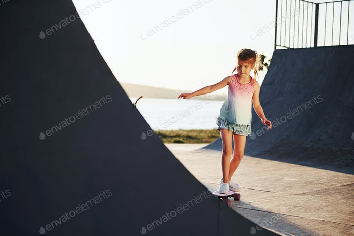 Sunny day. Kid have fun with skate at the ramp. Cheerful little girl